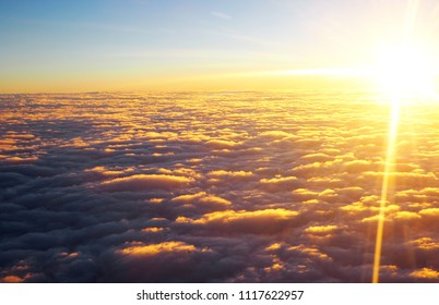 View of clouds at sunset from plane windowView of clouds at sunset from plane window