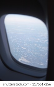 View of a cloudy landscape through an airplane window.