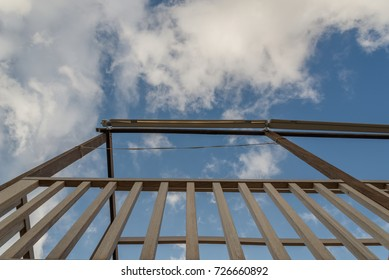 View of a cloudy sky under a wooden structure.