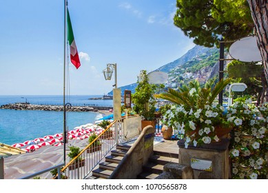 View of coast Amalfi, beach, sea and mountains with embankment decorated with flowers and palm trees and Italian flag of small town of Amalfi Coast with Gulf of Salerno, Campania, Italy.