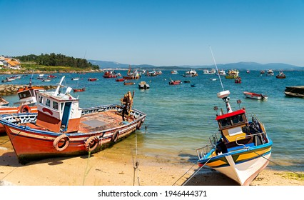 View of the coast and beach in Arousa island in the region of Galicia, Spain, with colorful fishing boats ashore and anchored in calm ocean waters.
