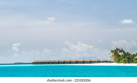 view of the coast of irufushi island with a lot of water bungalows, maldives