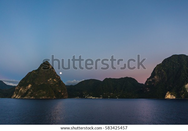 View of the coast of the island of St. Lucia on the deck of a cruise ship after sunset with the moon on the horizon