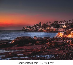 A view of the coast of La Jolla, San Diego in southern California against the red blue twilight sky, lit by the setting sun at low tide, painting the natural shores hues of orange and red.