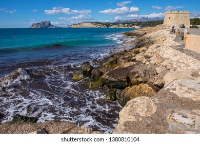 The view from the coastal town of Moraira, looking towards Calpe Rock and the town of Calpe in the Costa Blanca region of Spain.  The Castillo de Moraira, or Castle of Moraira, can also be seen.
