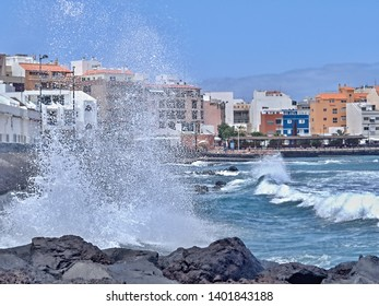 View of the coastal town of Puertito de Guimar Tenerife north, in front of it a very agitated Atlantic Ocean with heavy waves and splashing spray and a few black volcanic rocks
