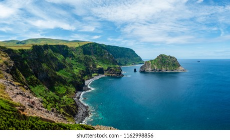 View to the coastline in Flores Island and a little islet on the ocean with some clouds in the sky