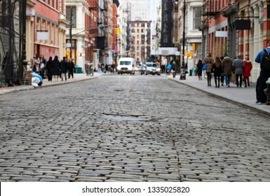 View of cobblestone covered Greene Street with bright sunlight background in the SoHo neighborhood of Manhattan, New York City