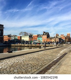 View of cobblestone street, harbor water, and colorful houses of Fells Point, Baltimore