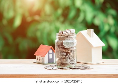 View Of coin stack with house model on green background, savings plans for housing, financial concept,Mortgage loading real estate property with loan money bank concept.Property Tax Concept
