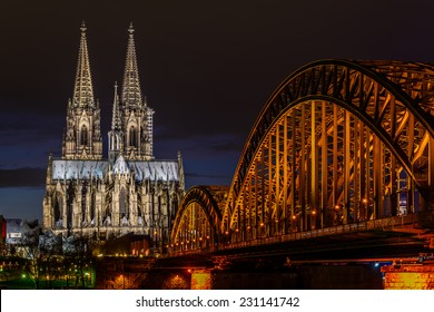 View of the Cologne Cathedral and Hohenzollern Bridge across the Rhine, Germany, at dusk