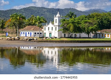 View of colonial church Igreja Nossa Senhora das Dores (Church of Our Lady of Sorrows) with water reflections and mountains in background, historic town Paraty, Brazil