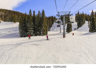 View of a Colorado ski slope on a nice winter day; skiers and snowboarders skiing down the slope to the base of a chairlift; trees and mountains in the background