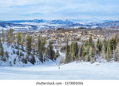 View of Colorado, USA, ski slope descending to resort town in winter; distant mountains and blue sky in background; view from the top of the slope