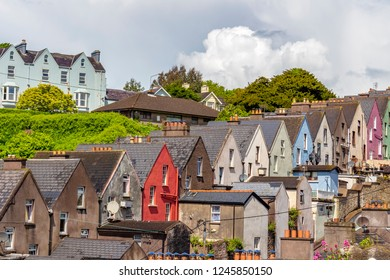 View of colored paired houses on the mountain slope, in the city of Cobh, Ireland.