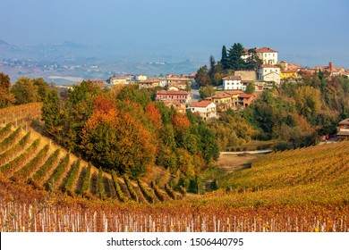 View of colorful autumnal vineyards on the hills of Langhe and small town on background in Piedmont, Northern Italy.