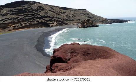 view of a colorful bay on the island of Lanzarote with black beach, redbrown rocks and blue water