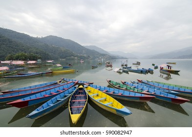 The view of colorful boats at Pokhara lake with mountain at the background, Nepal