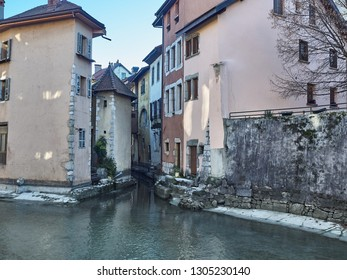 View of the colorful houses of Annecy reflecting into the water of the river Thiou during a sunny day