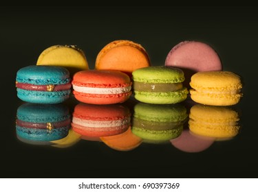 View of colorful macaroons and their reflections on black background