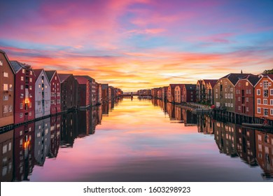 View of colorful timber houses surrounding river Nidelva in the city of Trondheim at sunset. View from Old Town Bridge. Trondelag county. Norway