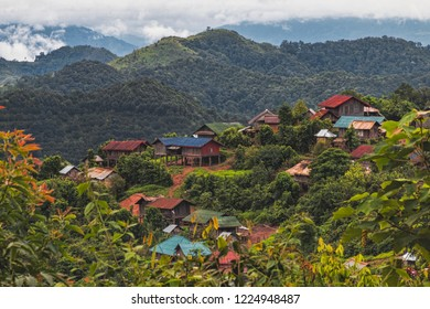 View of Colorful Traditional Akha Hill Tribe Village on Mountain Top in Nam Ha National Rain Forest. Skyline of Ethnic Village Framed by Mountains and Green Forest. (Luang Namtha, Laos).
