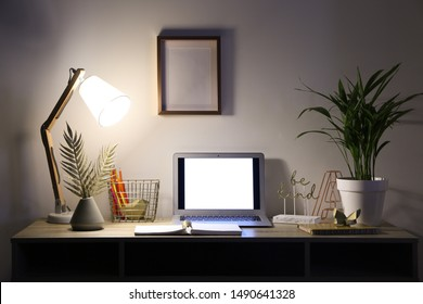 View of comfortable workplace with laptop in evening