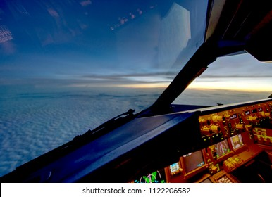 The view from commercial airplane, seen from captain seat in cockpit in the evening twilight during flying above the cloud over the ocean.