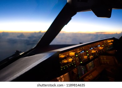 The view from commercial airplane, seen from captain seat in cockpit in the morning twilight during flying above the cloud over the sea. Modern aviation concept.