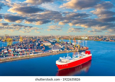 View commercial sea port on a Sunny day. Cargo ship Red against blue water. Transportation of goods by water transport. Berth with colorful containers. Commercial port infrastructure.