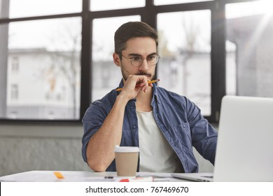 View of concentrated talented skilled male focused on screen of laptop computer, reads necessary information for creating budget report, drinks hot beverage. Attractive male freelancer keyboards text - Shutterstock ID 767469670