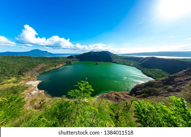 View of cones of Taal Volcano and the wind ruffled emerald green water in the Lake Taal on a sunny day in Tagaytay, Philippines.