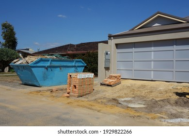 View of construction site with building material and equipment. The new build house has yellow sand, new bricks in front of big garage and old blue skip bin on driveway. Space to add text on the road.