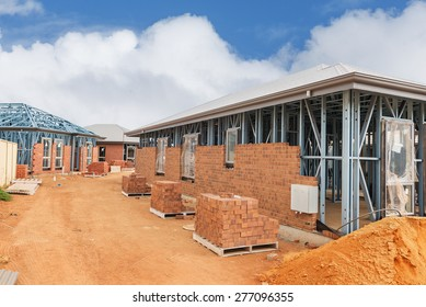 view of construction site with homes from brick with metal framing against a blue sky