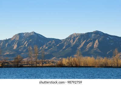 View of Coot Lake and the Flatirons Mountains golden morning sunlight in winter, with bare elms and cottonwoods on the far shore.