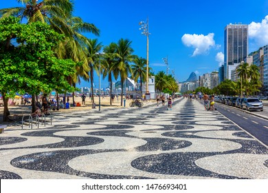 View of Copacabana beach with palms and mosaic of sidewalk in Rio de Janeiro, Brazil