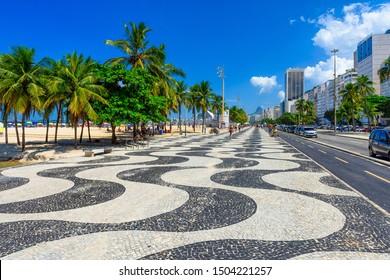 View of Copacabana beach with palms and mosaic of sidewalk in Rio de Janeiro, Brazil. Copacabana beach is the most famous beach in Rio de Janeiro. Sunny cityscape of Rio de Janeiro