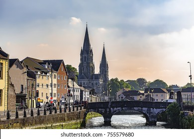View of Cork with bridge over Lee river and Saint Fin Barre's Cathedral in the far view at sunset, Ireland