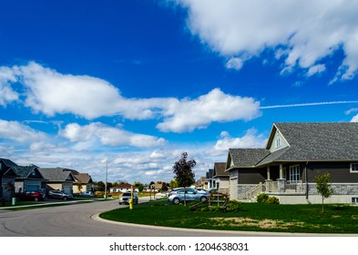 View from a corner of a new housing subdivision with a cloudy blue sky with a jet trail through a cloud