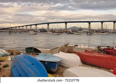 View of the Coronado Bay Bridge and shoreline boats at sunset in San Diego, California.