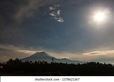 View of the Cotopaxi volcano on a cloudy, full moon night
