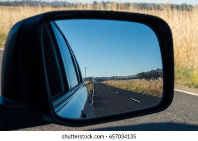 View of a country road in Victoria, Australia seen in a car rear view mirror