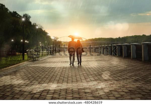 秋の夕暮れに雨の公園を歩く、傘の下に戻る夫婦の姿。明るい日没。