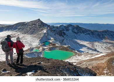 View with a couple of hikers at beautiful Emerald lakes on Tongariro Crossing track, Tongariro National Park, New Zealand