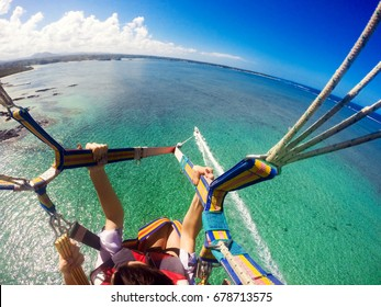 View of couple parasailing with the speed boat in the sea background.