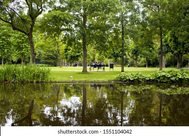 View of a couple sitting on a bench, people hanging out, trees, grass field and pond at Vondelpark in Amsterdam. It is a public urban park of 47 hectares. It is a summer day.