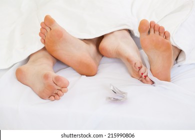 View of couple using contraception in bed