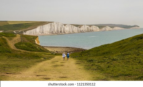 View of a couple walking down a pathway with the white cliffs and sea of seven sisters in the background, England, United Kingdom