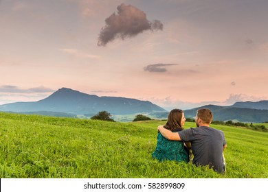View of a couple watching the sunset on a meadow and the Mountain Choc in background in Slovakia