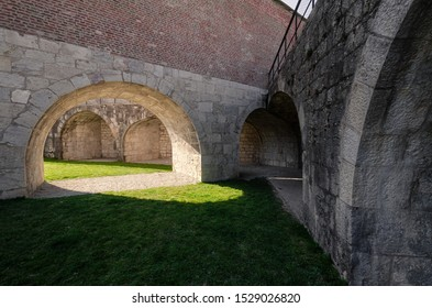 View of the courtyard of the old fortress. Skovoz an arch in a wall on a green lawn the sunlight falls. The yard is surrounded by thick stone walls. Citadel in the city of Besancon. France. Background